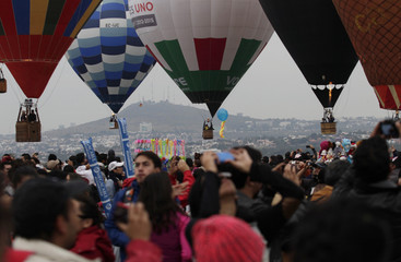 Visitors take pictures of hot-air balloons flying overhead during the 12th International Hot-Air Balloon Festival at the Metropolitano park in Leon