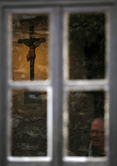 The cross is pictured through the window of the home of the three young shepherds in Fatima