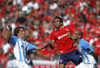 Independiente's Parra fights for the ball with Racing Club's Pelletieri and Aveldano during their Argentine First Division soccer match in Buenos Aires