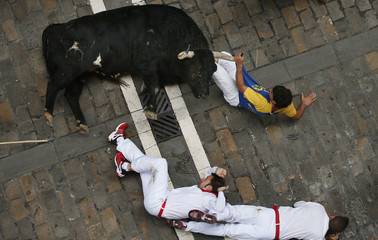 A runner holds the horn of an El Pilar fighting bull during the sixth running of the bulls of the San Fermin festival in Pamplona