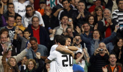 Real Madrid's Higuain congratulates Ronaldo on his first goal against Racing Santander during their soccer match in Madrid