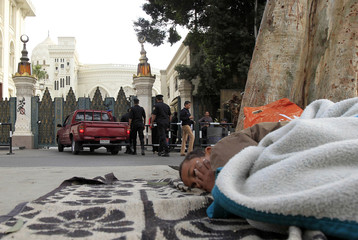 A boy sleeps during a sit-in in front of the presidential palace in Cairo
