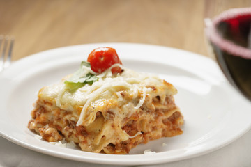 homemade lasagna with red wine on wood table, shallow focus