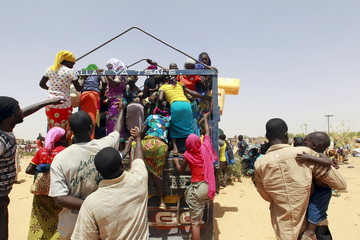 People displaced by the Boko Haram insurgence board a truck to travel back to their home states, after arriving in Nigeria, at Geidam, Nigeria