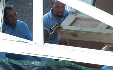 Still image taken from video show French gendarmes working on a crate in Saint-Denis