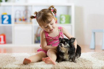 Little girl and small cute dog in the living room