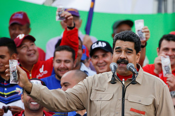 Venezuela's President Nicolas Maduro holds up a mock 100-bolivar bill depicting the president of the National Assembly Henry Ramos Allup, during a pro-government rally in Caracas
