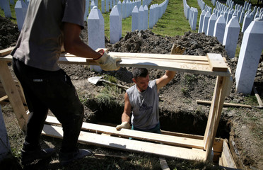 Workers dig graves at a memorial centre for Srebrenica Massacre victims in Potocari