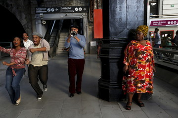 """Members of South Africa's Cape Town Opera dance and sing during performance to promote opera show """"Porgy and Bess"""" at Principe Pio train station in Madrid"""