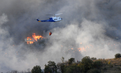 A helicopter works to extinguish a forest fire in Vina del Mar city, about 121 km (75 miles) northwest of Santiago