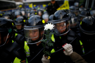 A man holding a flowers leans on a shield of a riot policeman as they march toward the Presidential Blue House during a protest calling for South Korean President Park Geun-hye to step down in central Seoul