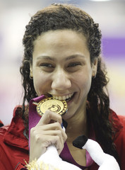 Farida Osman of Egypt celebrates after winning the gold medal at the Women's 100m Freestyle final at the Arab Games in Doha