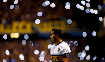 Boca Juniors' striker Carlos Tevez walks on the field as cell phone flash lights light up the background during their Argentine First Division soccer match against Tigre in Buenos Aires, Argentina