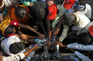 Demonstrators from tribes of various parts of Maharashtra state gather around a tanker to collect drinking water in bottles during a rally in Mumbai
