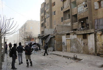 Men inspect a site hit by what activists said were barrel bombs dropped by forces loyal to Syria's President Bashar al-Assad in Masaken Hanano in Aleppo