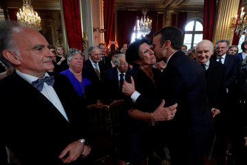 French President Emmanuel Macron kisses his mother Francoise Nogues as his father Jean-Michel Macron looks on during the handover ceremony at the Elysee Palace in Paris