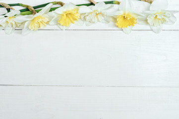 Frame of bright yellow daffodils in vase on white wooden table with copy space. Yellow and white narcissus. Greeting card. Top view