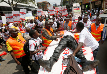 """A member of the civil society lies on top of a mock coffin stained with mock blood, as others chant slogans during a protest dubbed """"Stop extrajudicial killings"""" on the killing of human rights lawyer, Willie Kimani, his client and their driver in Nairobi"""