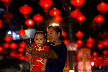 A woman and a boy take a picture on a street decorated with Chinese lamps to celebrate the Lunar New Year in Yangon