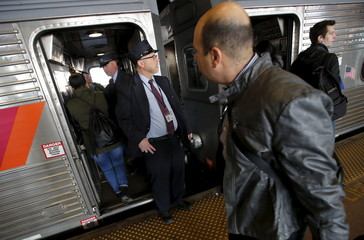 A conductor stands by a New Jersey Transit commuter train bound for New York City as passengers board at the Secaucus Junction station in Secaucus