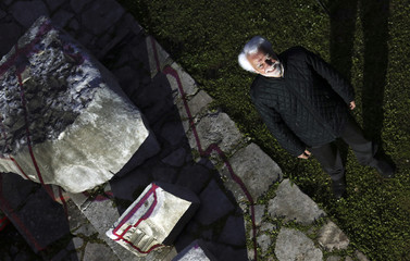 Lanciano, exhibition curator, poses before a reconstructed view of ancient Rome is projected on the walls of the Forum of Augustus in Rome