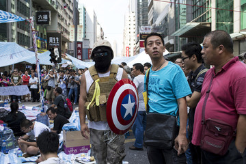 A protester of the Occupy Central movement carries a shield from the 'Captain America' comic book series as he stands on a main road at the Mong Kok shopping district in Hong Kong