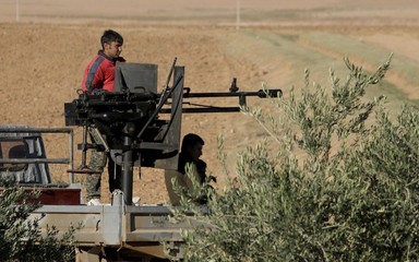 Kurdish People's Protection Units (YPG) fighters stand on a pick-up truck with a weapon installed on it in Ras Al-Ain countryside after claiming to have taken control of five villages and 20 farms from the Islamic State in the area