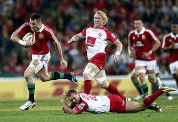 British and Irish Lions' player Bowe evades tackle of Queensland Reds' Cooper during game in Brisbane