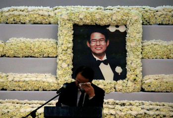 A man weeps in front of the picture of South Korean businessman Jee Ick-Joo, was allegedly killed by policemen inside the Camp Crame police camp, during a meomrial service in Quezon city Metro Manila