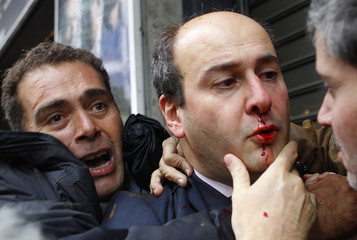 A bodyguard tries to save bleeding former conservative minister Hatzidakis after a mob of about 200 leftists attacked him in central Athens
