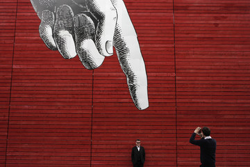 A man poses for a photograph under artwork of a large hand on a wall in central London