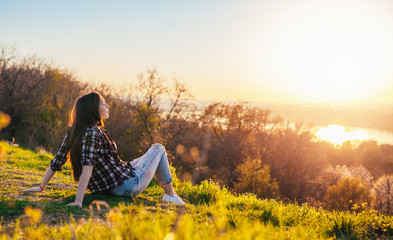 Woman relaxing on the sunset light on the top of the hill