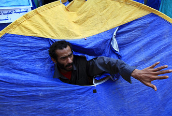An anti-government protester in a sit-in tent talks to his friend during a rally to demand the ouster of Yemen's President Ali Abdullah Saleh in Sanaa