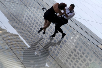 """Dancers rappel down the side of a building as part of a performance during a ribbon cutting ceremony to celebrate the opening of the flagship """"Hublot"""" store on Fifth Avenue in the Manhattan borough of New York"""