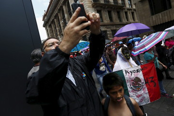 A woman holds a Mexico flag as a man takes a selfie picture during a march for Labor Day in Mexico City
