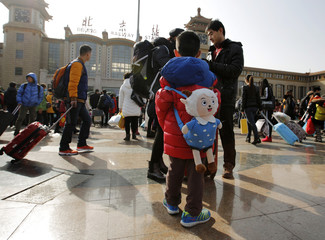 Boy carries a backpack in the shape of Xiyangyang, a cartoon character also known as Pleasant Goat, at a railway station in Beijing