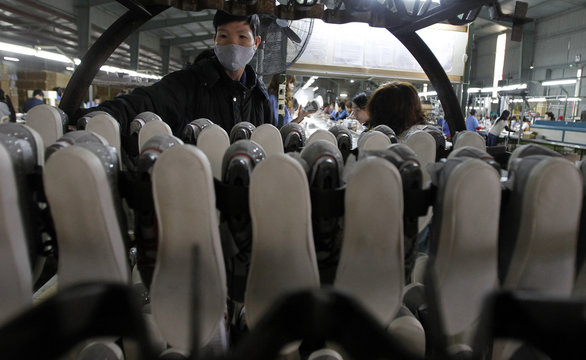 A man arranges shoes on a cart on an assembly line at a shoe factory in Tan Lap village