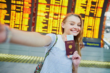 Girl in international airport, taking funny selfie with passport and boarding pass near flight information board