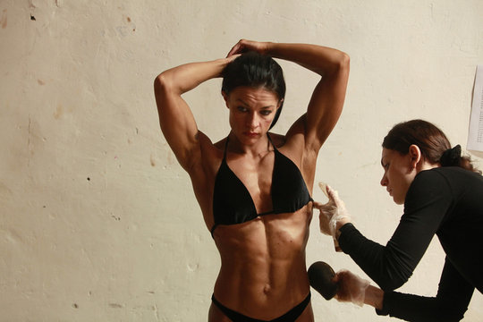 Participant has tanning lotion applied on her body during Eastern European Cup bodybuilding competition in Stavropol