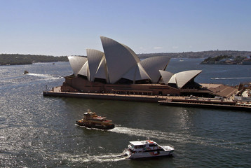 Boats cross each other in front of the Sydney Opera House