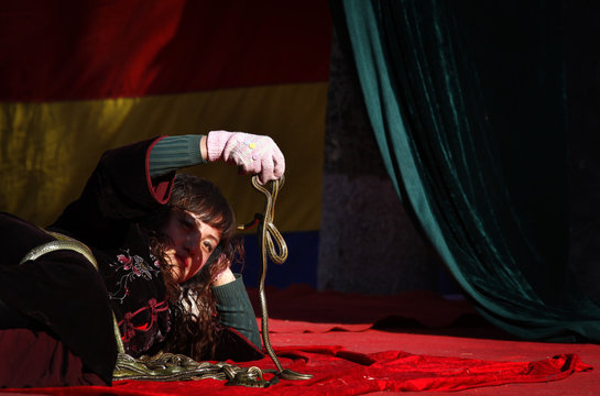 A woman covered with live snakes lies on a small stage as she showcases acts of magic and feats of unusual physical abilities at the temple fair in Ditan Park