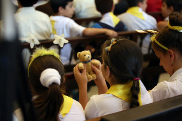 A child wearing the colours of the Vatican holds a teddy bear during a mass at the Havana's Cathedral, Cuba