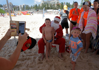 A surf life saver dressed as Santa Claus poses for a souvenir photo while delivering early Christmas gifts to children at Sydney's Coogee beach
