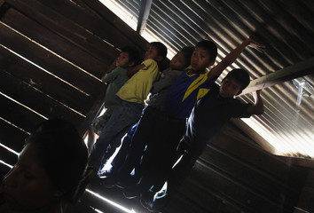 Boys look at coffin containing skeleton of Martina Rojas, who disappeared during internal armed conflict, in house of Rojas' son Mario Chen, in Rabinal