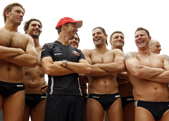 British McLaren F1 driver Jenson Button poses with members of the Hungarian water polo team during a training session in Budapest