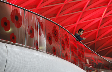 A man uses his phone by commemorative poppy designs at King's Cross Station in London