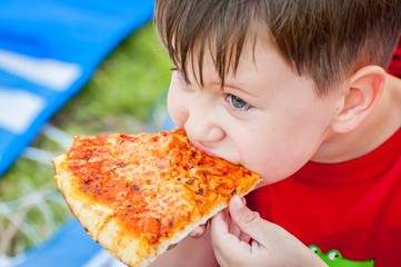 Cute little kid taking a bite from a delicious margarita pizza slice.
