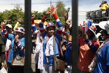 Anti-government protesters cheer as they arrive at an air force base in Bangkok