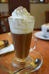 Viennese coffee with whipped cream on glass cup.