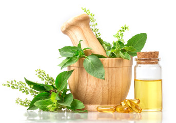 Sweet basil and hot basil in wooden mortar with essential oil and supplement, alternative herbal medicine concept